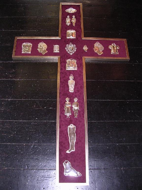 Large Crucifix frame housing silver votives - mounted on red velvet board.