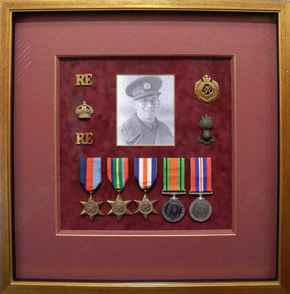 Collection of medals and badges, with a photograph